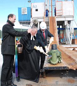 Bürgermeister Michael Sedlmair und Pfarrer Werner Blechschmidt rücken dem Meißel zu Leibe, Pfarrer Markus Brunner assistiert mit Weihwasser (von rechts)